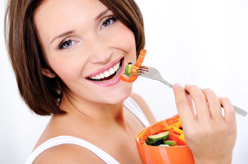 happy attractive woman eats vegetable salad